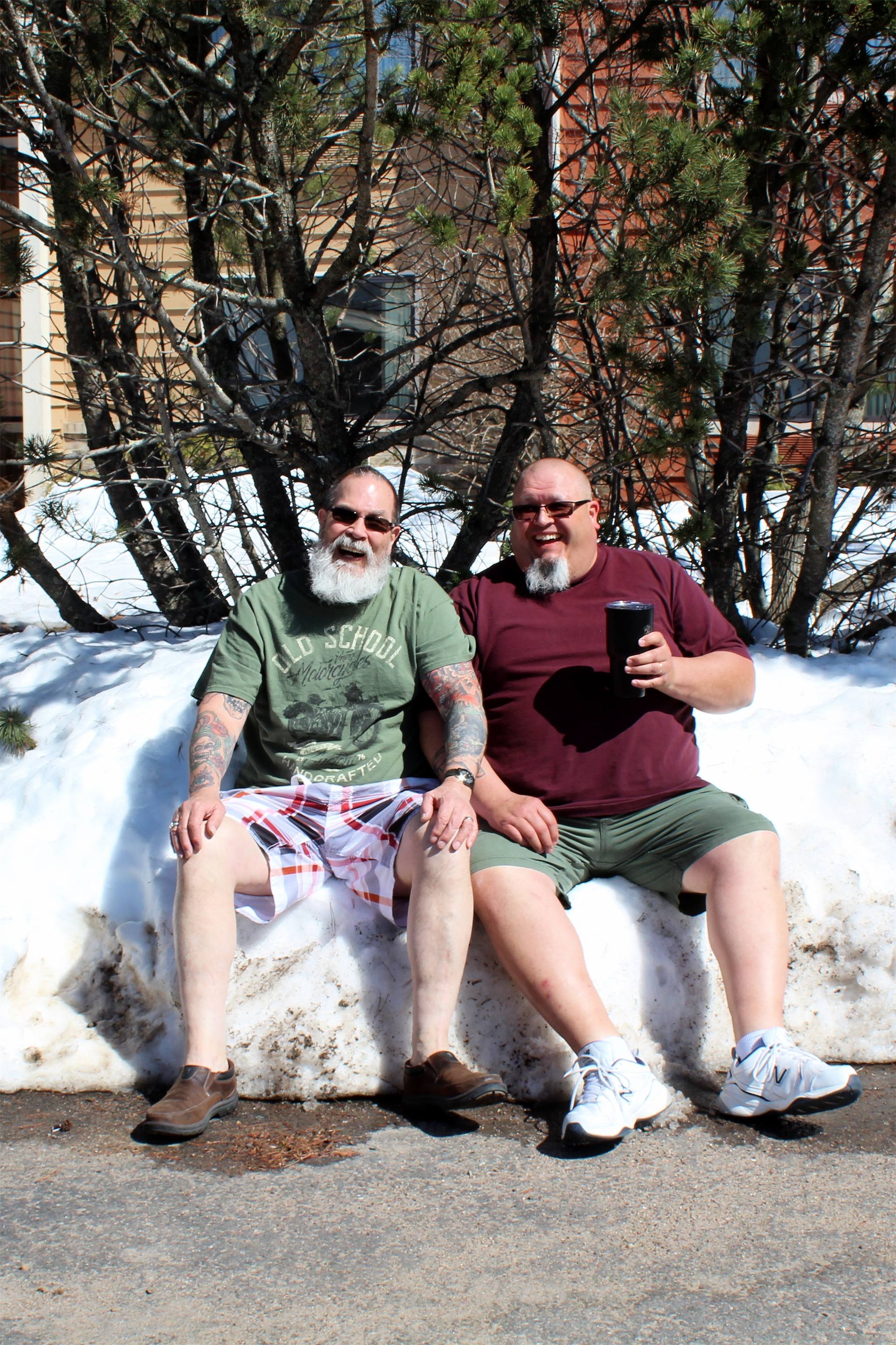 Wing and Mark take a seat in the snowbank at the AmericInn while enjoying the sun in Minocqua. Kim Johnson photo