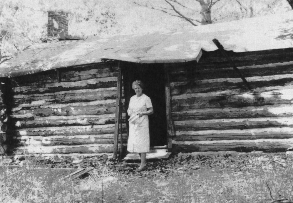 The log cabin school at Coon's Resort. Teacher Minnie Hewitt provided instruction. The woman shown here was a guest at the resort. Courtesy of Boulder Junction Area Historical Society