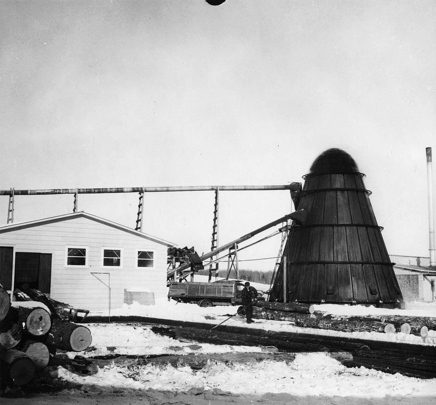 Hot pond, refuse burner and new sawmill housing for the new band saw built at the Pukall Lumber Company mill, Woodruff. Taken in January 1955. Wisconsin Department of Natural Resources photo