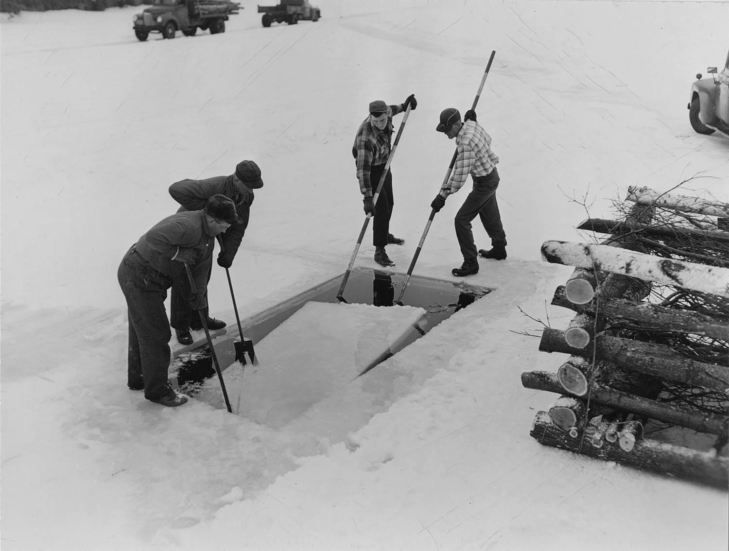 Pushing a block of ice out of a hole to slide fish brush shelter into Big Carr Lake. Photo dated 1956. Wisconsin Department of Natural Resources photo