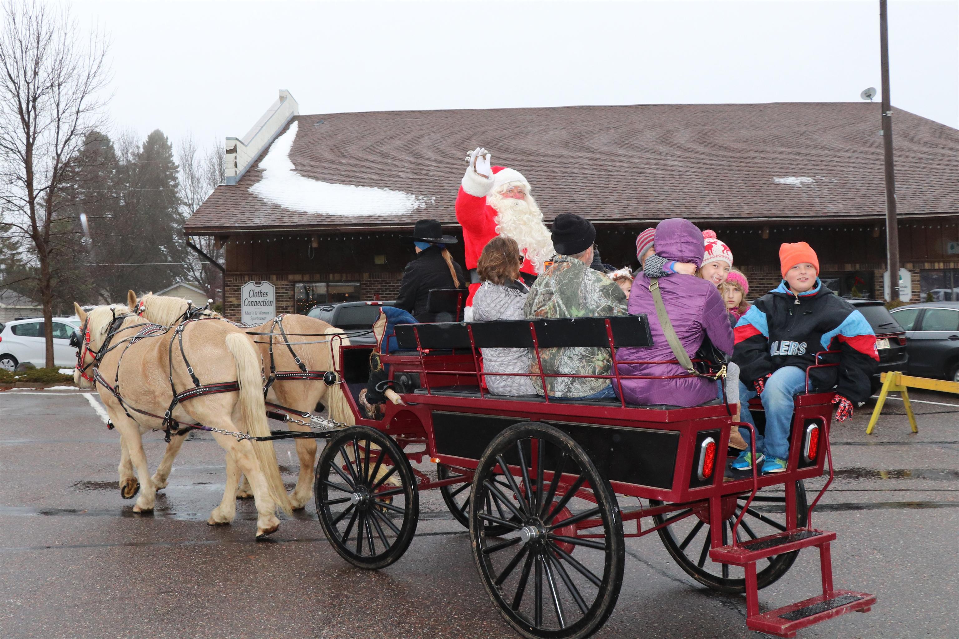 After arriving in Minocqua, Santa rides through town in a horse-drawn wagon. Kim Johnson photo