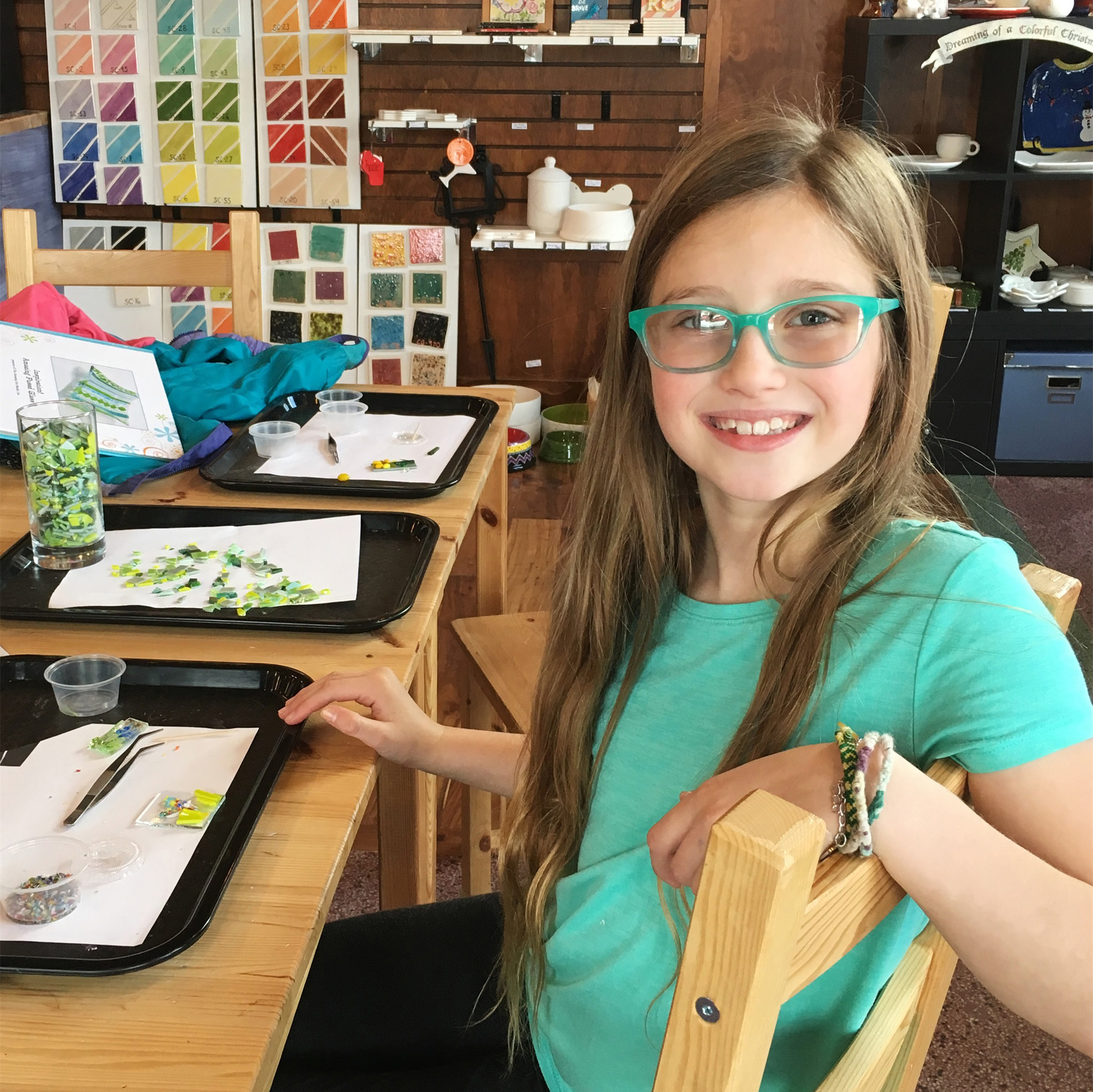 Charlotte is all smiles as she works on stained glass at Earth Goods in Minocqua. Kim Johnson photo